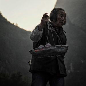 In south China, on the banks of the Li River, a street vendor offers her products for sale.