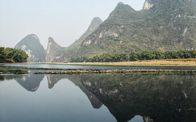 In south China, karst mountains are reflected in the Li River.