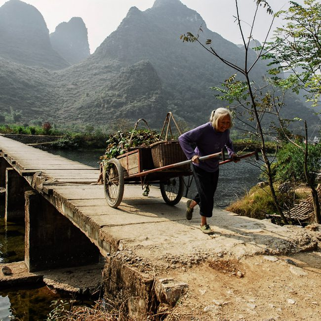 In south China, a woman with her cart crosses a bridge near Yangshuo.