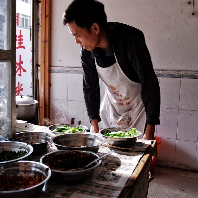 A cooker is preparing a chinese meal in a small shop around Yangshuo.