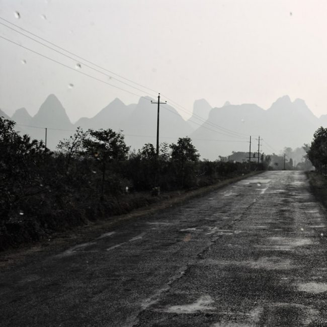 In south China, the road from Guilin to Yangshuo in the rain from the window of a minibus.