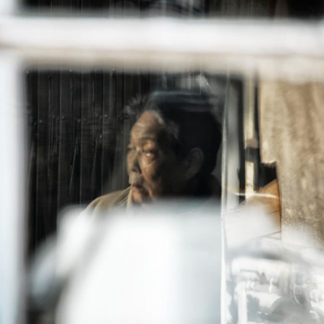 Reflection of an old man in a restaurant at Longji in southern China.
