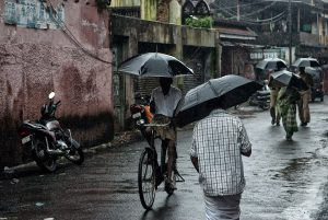 Street scene during monsoon in fort Kochi, an umbrellas' balet, South India