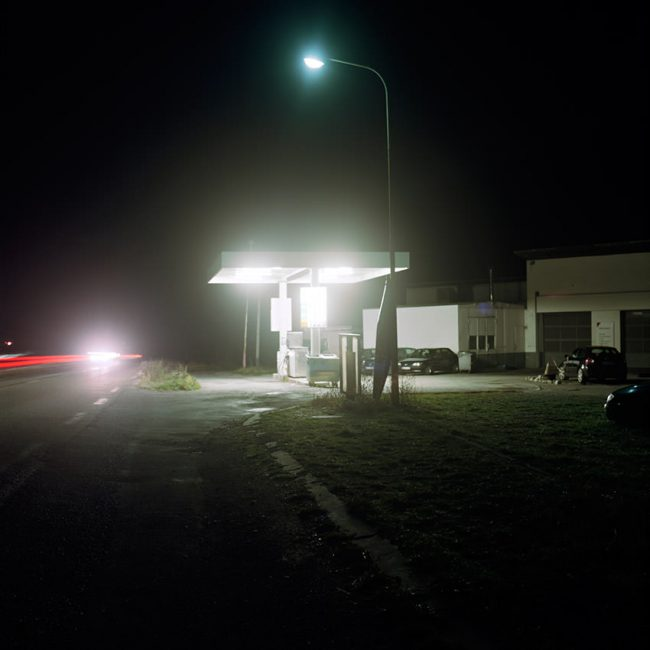 A gas station is lit at night on the Route Napoleon.