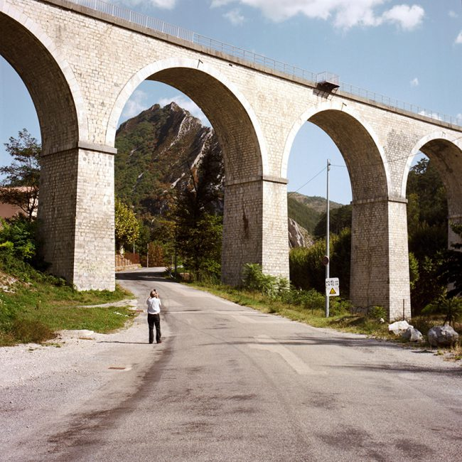 A tourist takes a picture of a bridge in Sisteron.