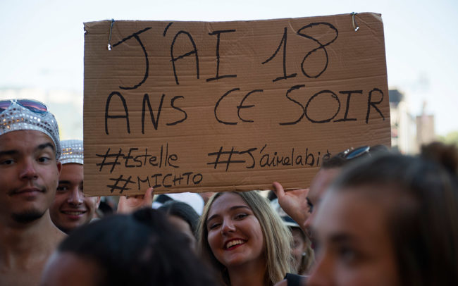 A young festival-goer shows a sign in Musilac