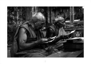 Two old monks are reading prayers to Thiksey.Deux vieux moines sont en train de lire des prières à Thiksey.