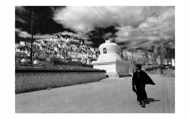 A young Buddhist monk walks below the village of Thiksey, Ladakh.Un jeune moine bouddhiste marche en contrebas du village de Thiksey, au Ladakh.