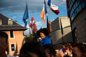 Un enfant est porté par son père avec un drapeau français.