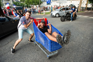 Deux jeunes sont dans un charriot, heureux.