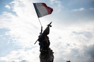 A homme est monté sur une statue avec un drapeau français.