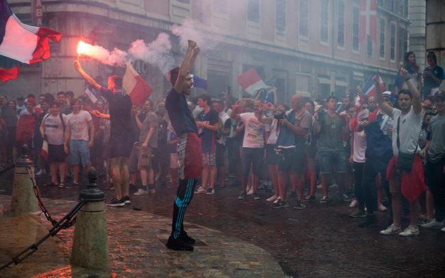 Un homme lève les deux bras en l'air en signe de victoire.