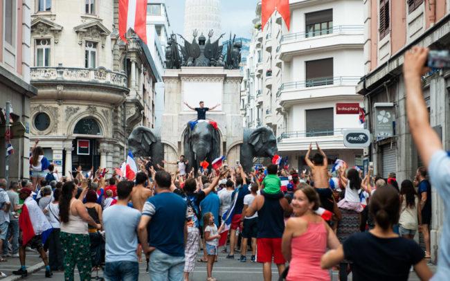 Un homme lève les deux bras en l'air en signe de victoire en haut d'un éléphant.
