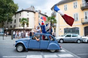 Des gens avec des drapeaux français sont dans une vieille 2CV dans les rues de Chambéry.