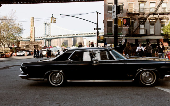 An old car is crossing the streets of Brooklyn.