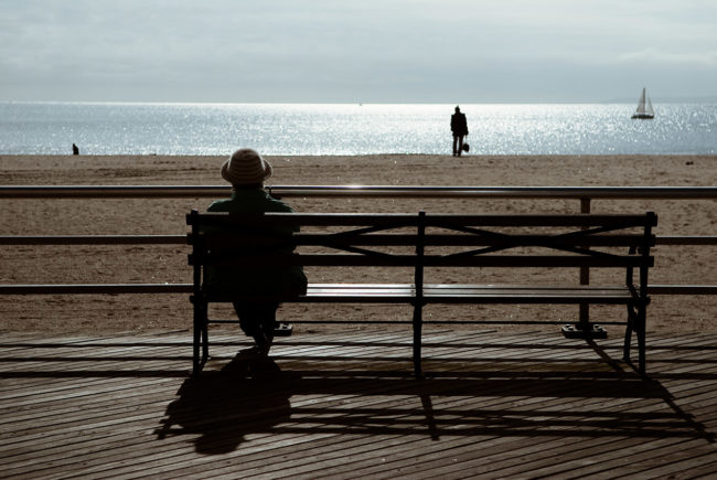 The woman on a Coney island's boardwalk bench.