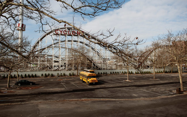 A yellow bus is parked in front of the Cyclone attraction at Coney Island.