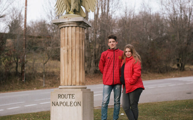 A couple of young bikers pose in front of the eagle, symbol of the Napoleon road.