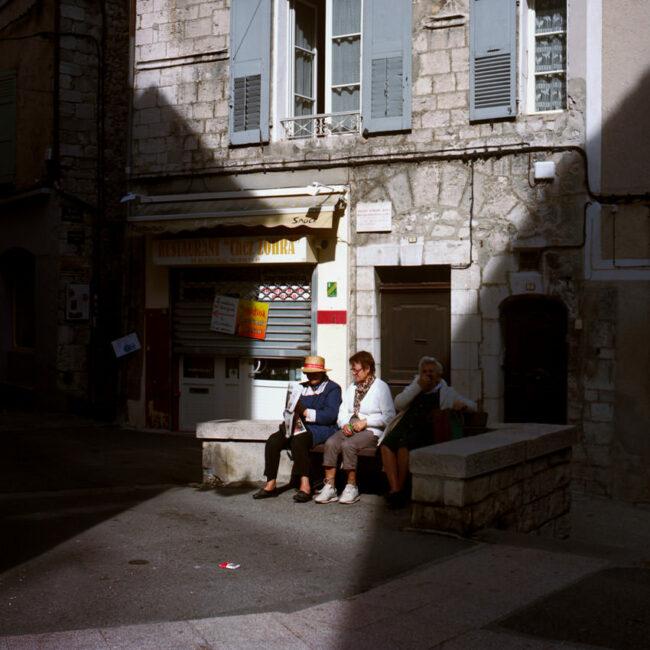 3 elderly people are sitting on a bench in Sisteron.Trois vieilles dames sont assises sur un banc de Sisteron.