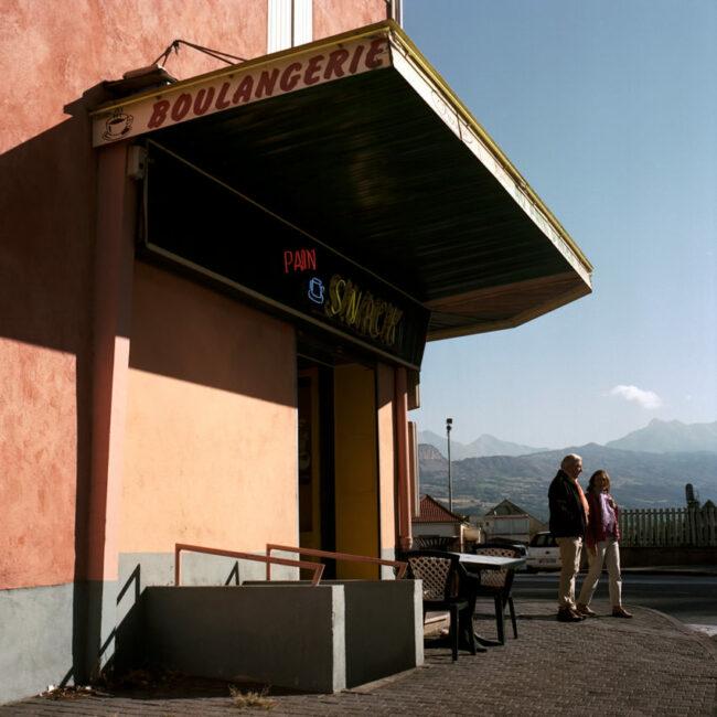A couple walks and passes in front of a bakery in Gap.Un couple marche et passe devant une boulangerie à Gap.